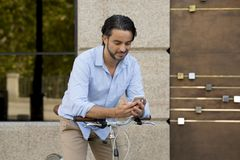 Young happy man smiling using mobile phone on vintage cool retro bike. Young happy attractive hispanic man in casual trendy clothes smiling cheerful using mobile stock photos