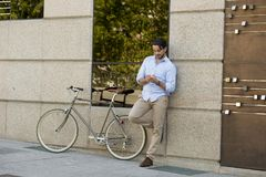 Young happy man smiling using mobile phone on vintage cool retro bike Royalty Free Stock Photo