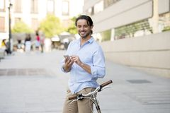 Young happy man smiling using mobile phone on vintage cool retro bike. Young happy attractive hispanic man in casual trendy clothes smiling cheerful using mobile stock photography