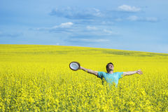 Young happy man standing on a meadow with raising hands and looking to a sky. Young happy man standing on a meadow with raising hands and looking to a sky Royalty Free Stock Photos