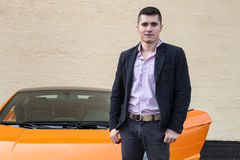 Young happy man standing near luxury sport car. Against the wall on the outdoors parking lot royalty free stock photography