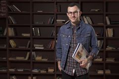 Young happy man student holding book in front of the bookcase Royalty Free Stock Photo