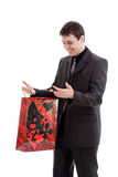 Young, happy man in a suit, looks in the bag. Young, happy man in a suit, looks in the bag, isolated on a white background Royalty Free Stock Photos