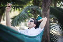 Young happy man in sunglasses relaxing on hammock between palm trees uses mobile phone takes selfie stock image