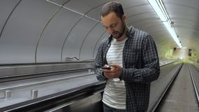 Young happy man surfing internet on his phone while standing on escalator. Medium shot.Young happy man surfing internet on his phone while standing on escalator stock video