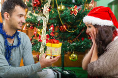 Young happy man surprises his girlfriend with Christmas gift stock photography