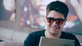 Young happy man with tablet computer sitting in cafe. stock video footage