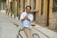 Young happy man taking selfie with mobile phone on retro cool vintage bike. Young happy attractive hispanic man in casual trendy clothes smiling cheerful using royalty free stock images