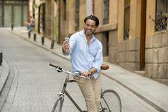 Young happy man taking selfie with mobile phone on retro cool vintage bike. Young happy attractive hispanic man in casual trendy clothes smiling cheerful using royalty free stock photos