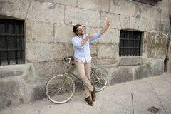 Young happy man taking selfie with mobile phone on retro cool vintage bike Royalty Free Stock Image