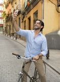Young happy man taking selfie with mobile phone on retro cool vintage bike. Young happy attractive hispanic man in casual trendy clothes smiling cheerful using stock photos