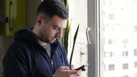 Young, happy man texting on smartphone by window at home stock video