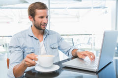 Young happy man typing on the laptop while holding his coffee Stock Photos