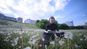 Young happy man using tablet in the park, sitting on the grass in dandelions, smiling and laughing. stock video