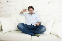 Young happy man watching television in disbelief and shock face expression Stock Photo