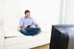 Young happy man watching television smiling and laughing in sofa. Young happy man watching tv lying at home living room sofa with remote control looking relaxed Stock Photos
