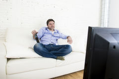 Young happy man watching television smiling and laughing in sofa. Young happy man watching tv lying at home living room sofa with remote control looking relaxed Royalty Free Stock Photo