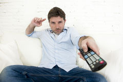 Young happy man watching tv sitting at home living room sofa looking relaxed enjoying television Royalty Free Stock Image