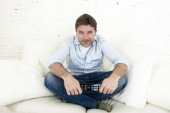 Young happy man watching tv sitting at home living room sofa looking relaxed enjoying television Royalty Free Stock Photo