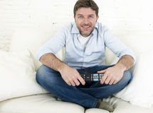 Young happy man watching tv sitting at home living room sofa looking relaxed enjoying television Stock Images