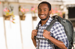 Young happy man wearing casual clothes and backpack posing for camera, smiling, garden environment, backpacker concept Stock Image