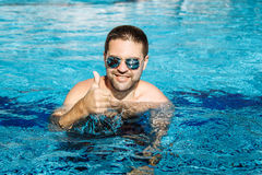 Young happy man wearing sunglasses in the swimming pool gesturin. G thumb up Royalty Free Stock Photos