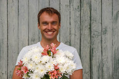 Young happy man with white flowers on wooden background Royalty Free Stock Photo
