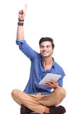 Young happy man winning and pointing up. While sitting and holding a tablet pad computer Royalty Free Stock Photography