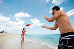 Young happy man and woman playing with frisbee. Boyfriend and girlfriend playing with frisby on tropical beach. Horizontal shape, copy space Stock Photos