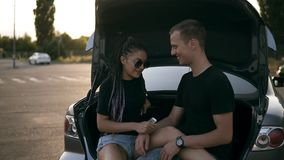 Young happy man and woman are sitting together in the open car trunk. Smiling, joyful couple caress each other, laughing. Sun shines on the background stock video footage