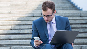 Young happy man working with mobile phone and tablet, horizontal portrait. Stock Images