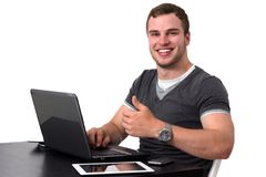 Young happy man working on pc. Happy man using pc and smiling while doing thumb up Royalty Free Stock Images