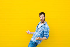 Young happy man on yellow Stock Images