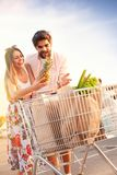 Young happy couple pushing shopping cart. Young happy men pushing shopping cart with his girlfriend outdoor Stock Photography