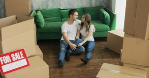 Young couple very happy and excited about moving into new apartment. Young happy millennial couple students move into their first new owners home. Simple white stock video