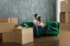 Young happy millennial couple students move into their first new owners home. Simple white background of urban apartment royalty free stock photo