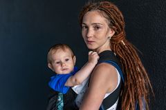 Young happy mom with baby son in ergo backpack travel together. Dark wall on the background. Concept of modern parents. Young happy mom with baby son in ergo royalty free stock image