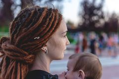 Young happy mom with baby son in ergo backpack travel together. Sunny summer day in the Park. Concept of modern parents. Young happy mom with baby son in ergo royalty free stock images