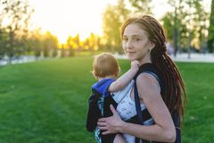 Young happy mom with baby son in ergo backpack travel together. Sunny summer day in the Park. Concept of modern parents. Young happy mom with baby son in ergo stock photos