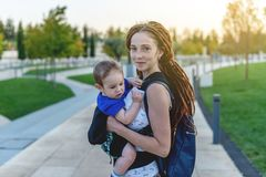 Young happy mom with baby son in ergo backpack travel together. Sunny summer day in the Park. Concept of modern parents. Young happy mom with baby son in ergo stock image