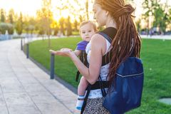 Young happy mom with baby son in ergo backpack travel together. Sunny summer day in the Park. Concept of modern parents. Young happy mom with baby son in ergo royalty free stock image