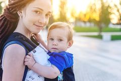 Young happy mom with baby son in ergo backpack travel together. Sunny summer day in the Park. Concept of modern parents. Young happy mom with baby son in ergo royalty free stock photo