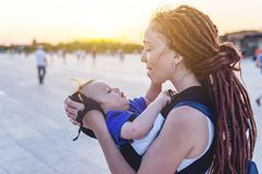 Young happy mom with baby son in ergo backpack travel together. Sunny summer day in the Park. Concept of modern parents. Young happy mom with baby son in ergo stock images