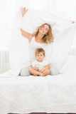 Young happy mother and baby child in bed at h Stock Photos