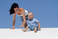 Young happy mother and child on blue sky bac Royalty Free Stock Photos