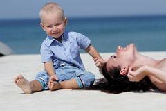 Young happy mother and child on blue sky bac Royalty Free Stock Images