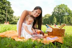 Young happy mother with daughter in the park picnicking Stock Photos
