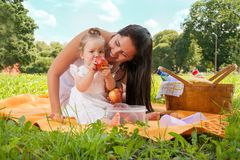 Young happy mother with daughter in the park picnicking Royalty Free Stock Photo