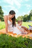 Young happy mother with daughter in the park picnicking Royalty Free Stock Image