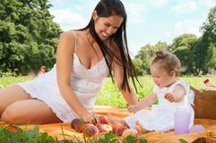 Young happy mother with daughter in the park picnicking Royalty Free Stock Photos